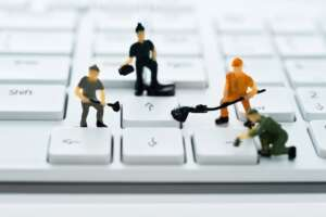 A group of figurines cleaning computer keyboard